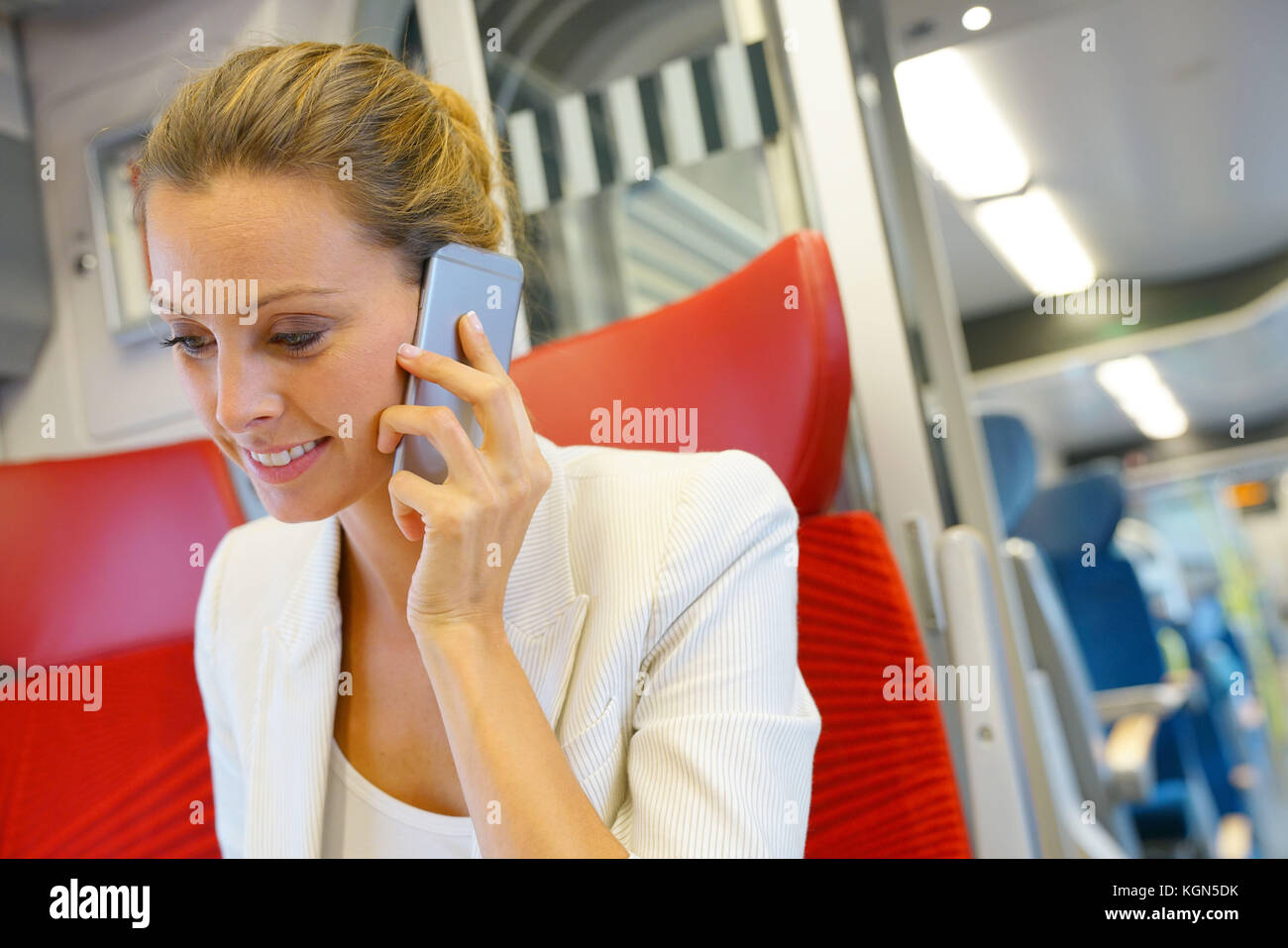 Businesswoman in train working on laptop and talking on phone - Stock Image