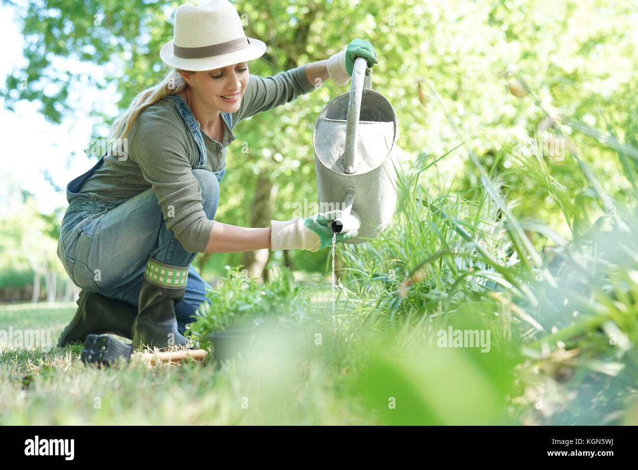 Blond woman with hat gardening - Stock Image