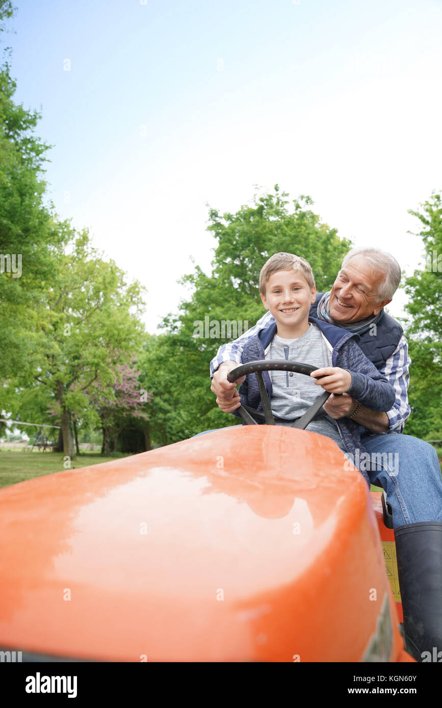 Senior man with grandkid riding on lawnmower - Stock Image