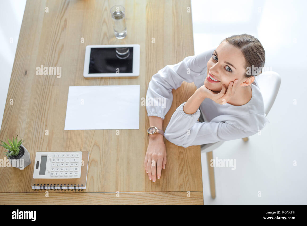 Smiling businesswoman at desk in office Stock Photo