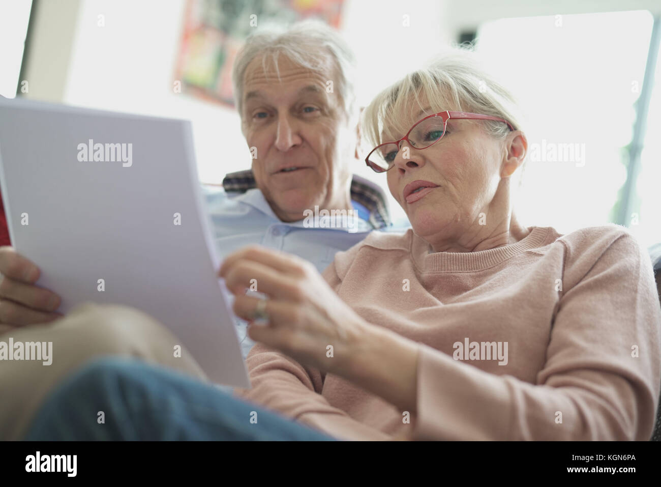 Senior couple in sofa reading official documents - Stock Image