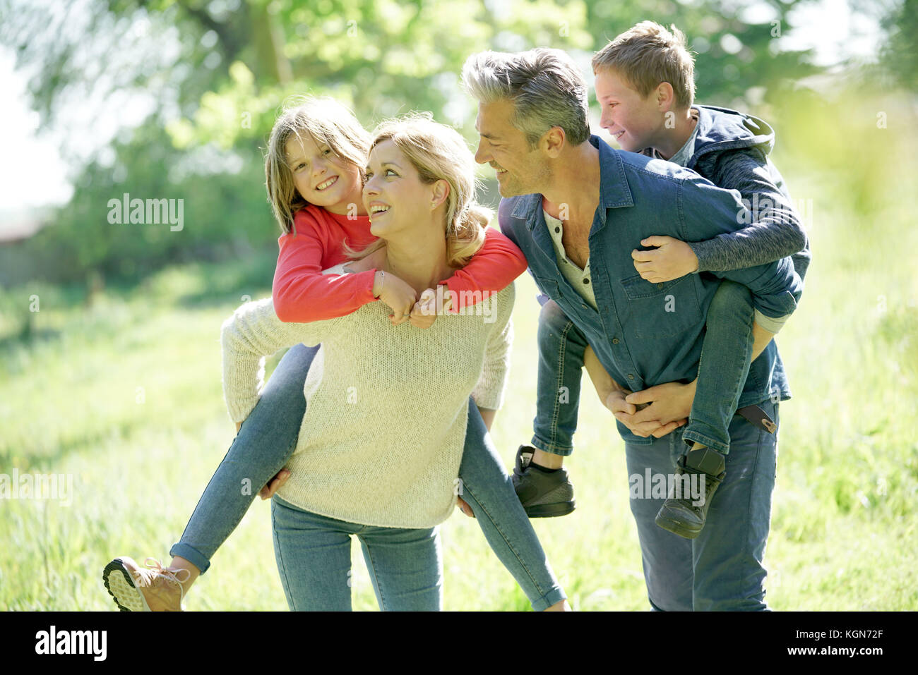 Parents giving piggyback ride to kids in countryside - Stock Image