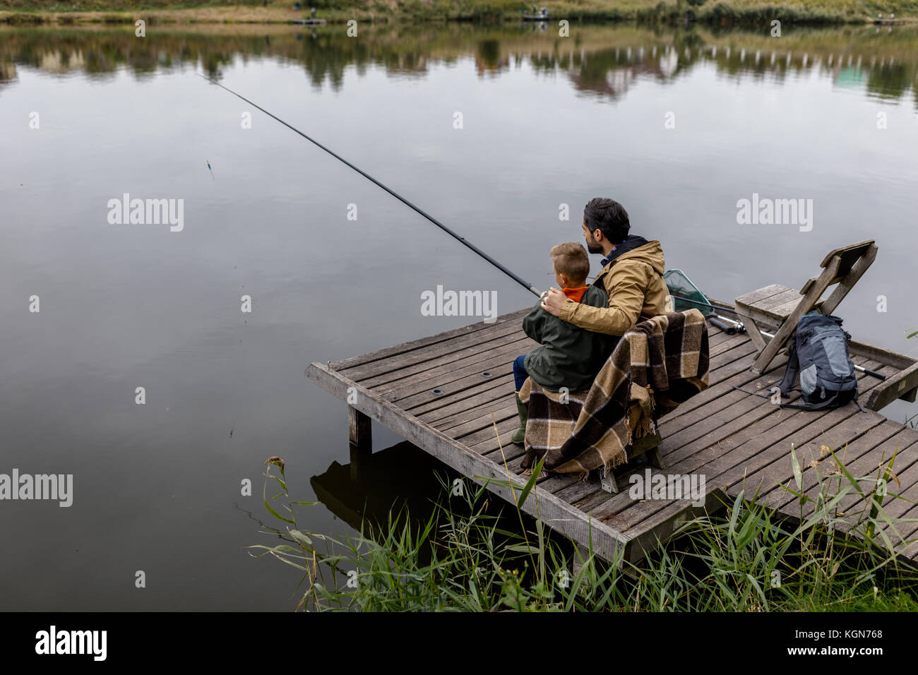 father and son fishing on pier - Stock Image