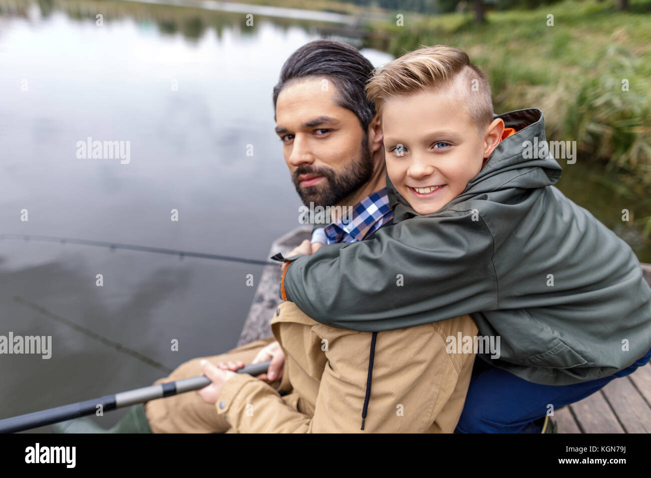 father and son fishing with rods  - Stock Image