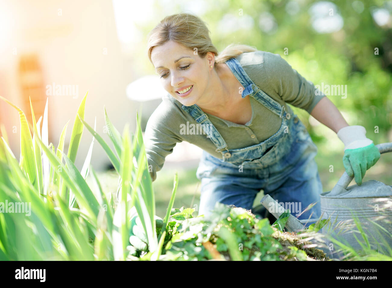Smiling blond woman gardening - Stock Image