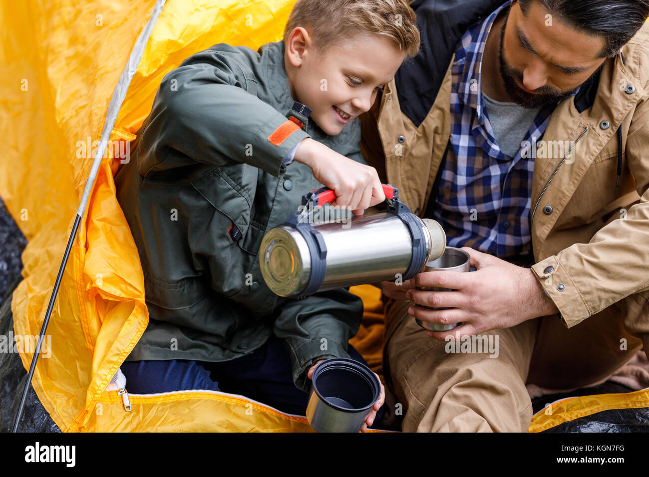 son with thermos in camping - Stock Image