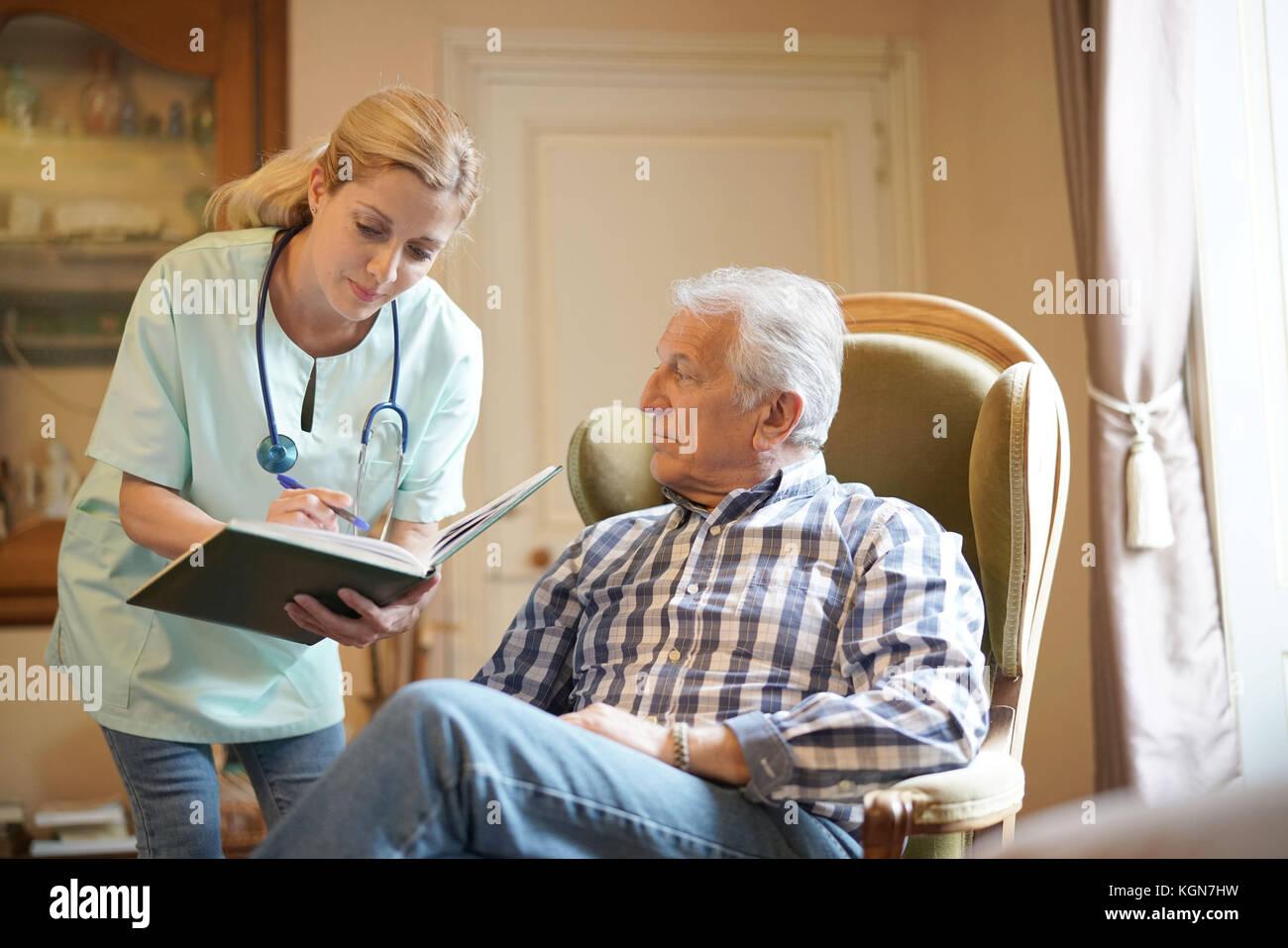 Nurse checking senior male patient results Stock Photo