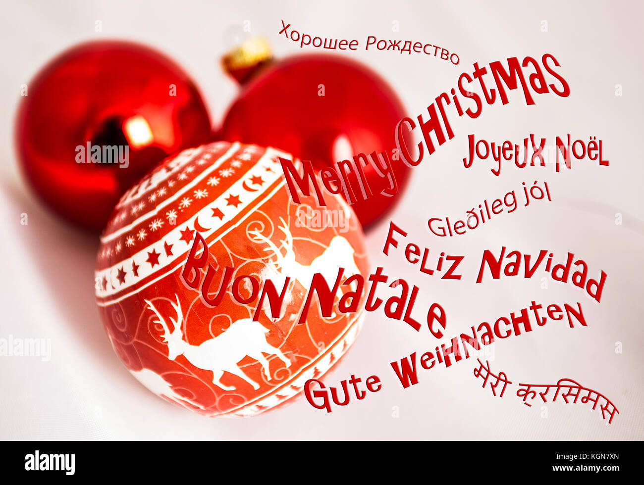 Group of christmas tree decorations in studio on white background with greeting in many languages. - Stock Image