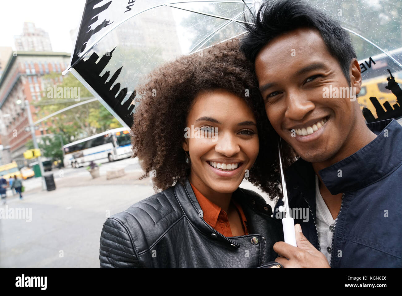Ethnic couple walking in New york city street on rainy day - Stock Image