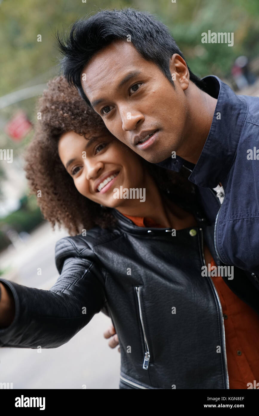 Couple calling for taxi cab in the city - Stock Image