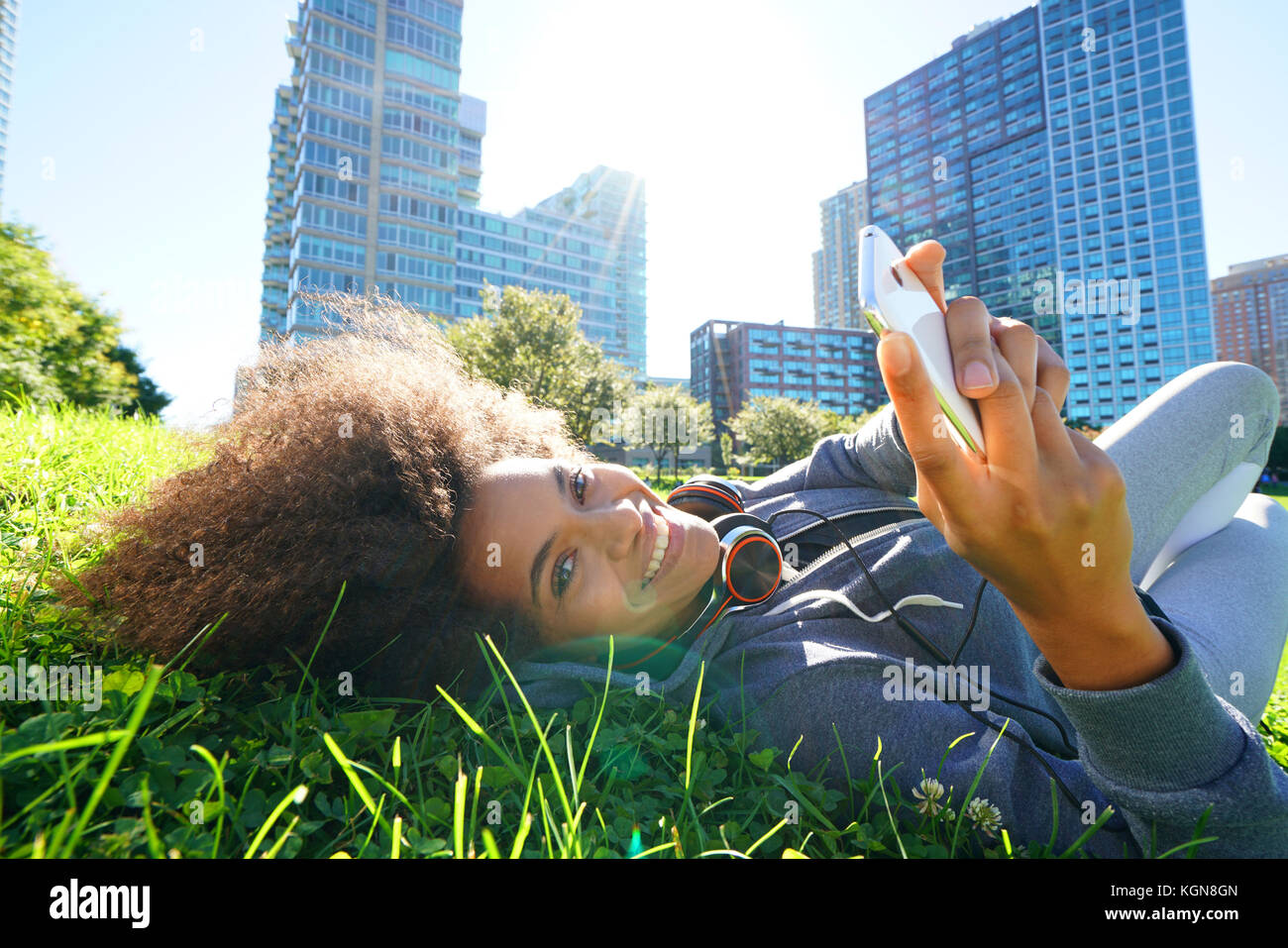 Portrait of mixed race girl laying in park using smartphone Stock Photo