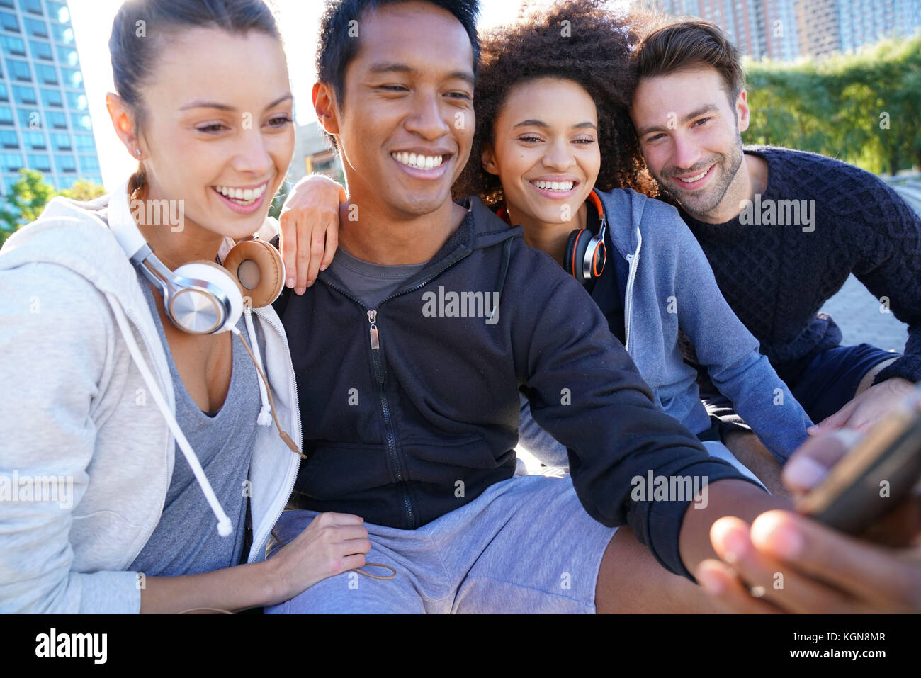 Group of friends in casual outfit taking selfie picture with smartphone - Stock Image