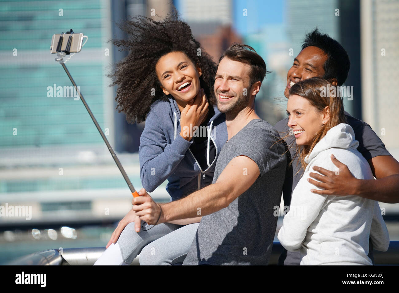 Group of friends taking selfie picture, Manhattan in background - Stock Image