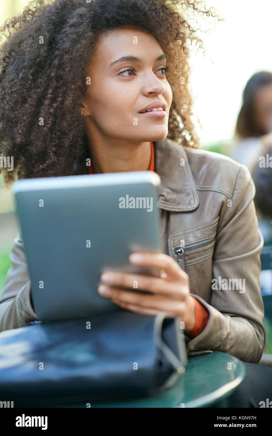 Businesswoman sitting in park, working on digital tablet - Stock Image