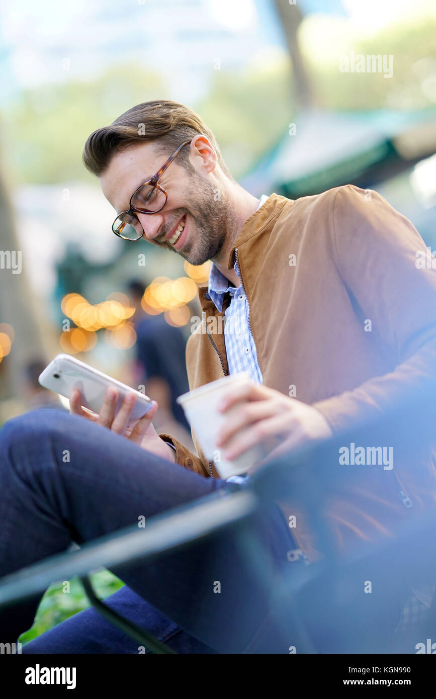 Businessman talking on phone sitting in park - Stock Image