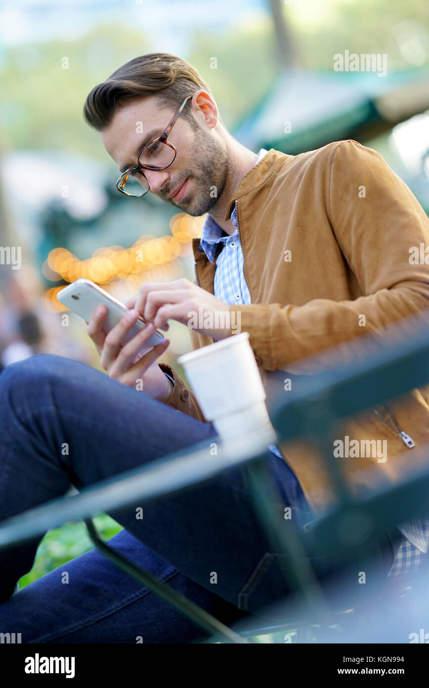 Businessman talking on phone sitting in park Stock Photo