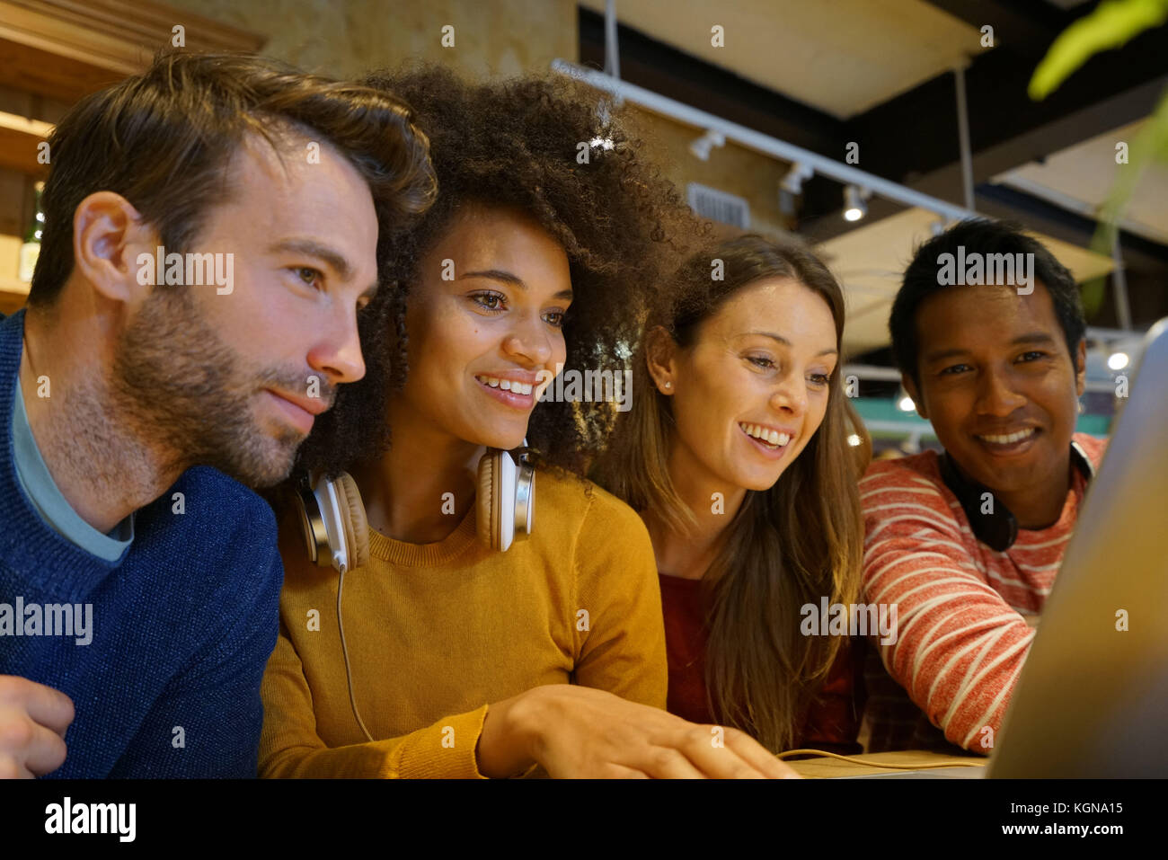 Group of friends websurfing on laptop in coffee shop - Stock Image