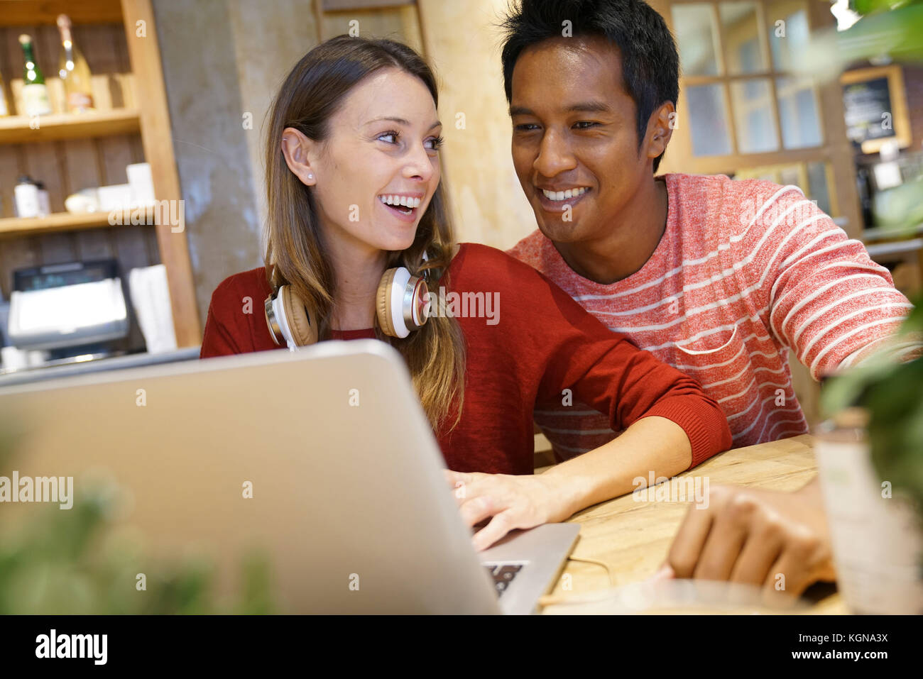 Couple in restaurant connected on internet with laptop - Stock Image