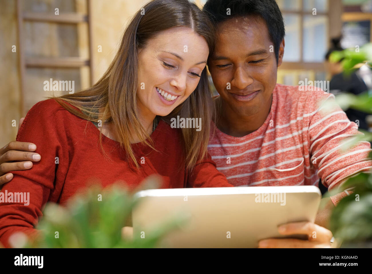 Couple in restaurant connected on internet with digital tablet - Stock Image