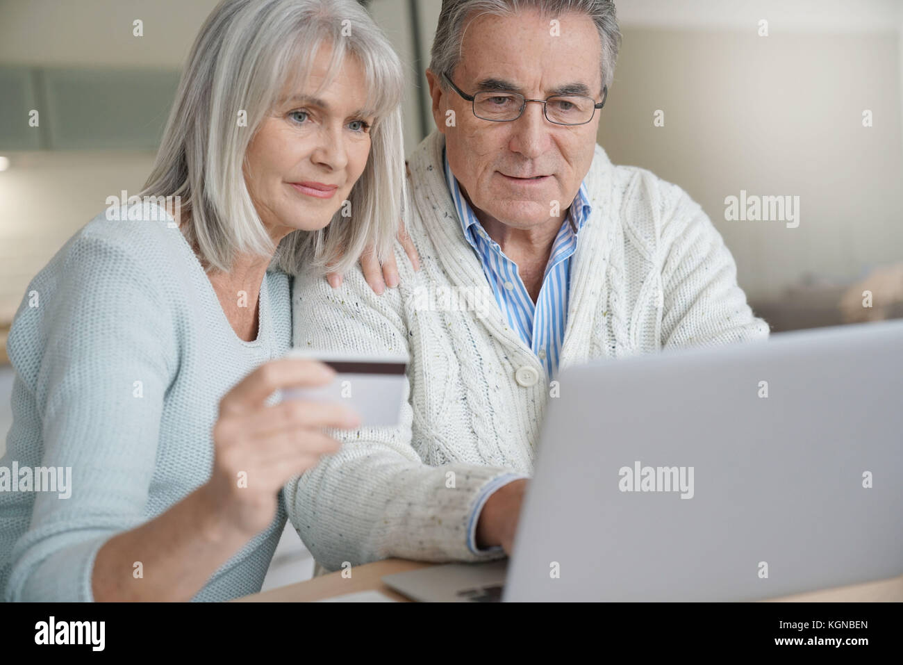 Senior couple buying on internet with credit card - Stock Image