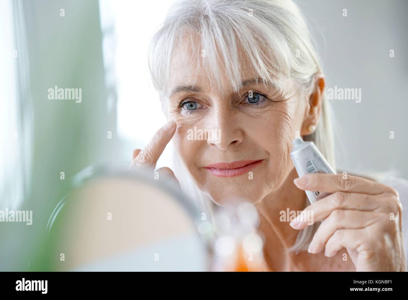 Portrait of senior woman applying anti-aging cream - Stock Image