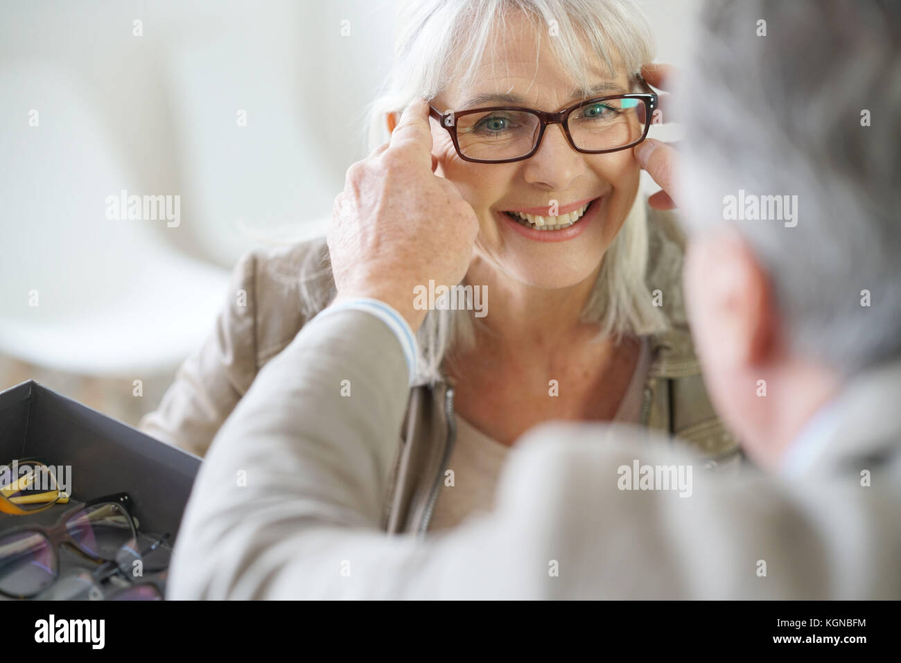 Senior woman in optical store trying eyeglasses on - Stock Image