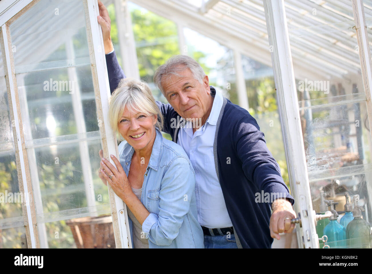 Senior couple standing by greenhouse in garden - Stock Image