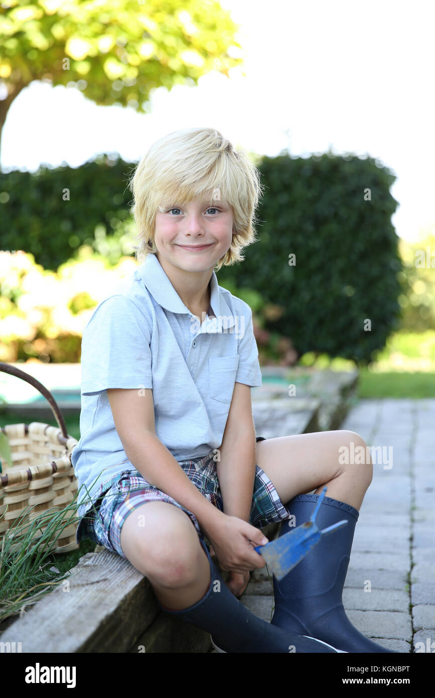 Portrait of cute 7-year-old boy in vegetable garden - Stock Image