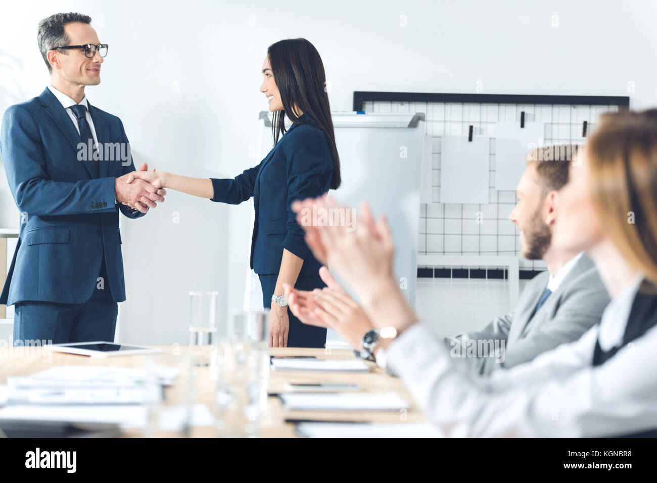 boss shaking hand of manageress - Stock Image