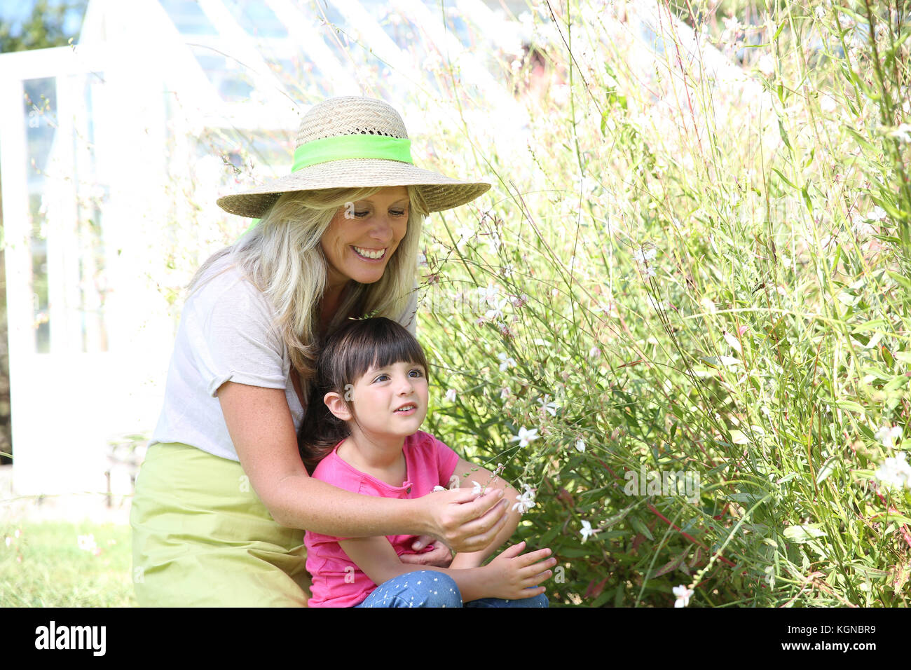 Mother and daughter having fun in aromatic garden - Stock Image