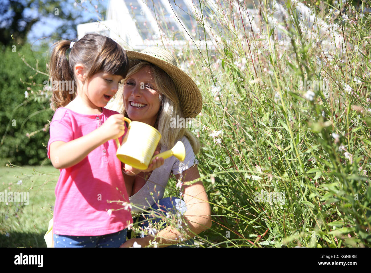 Woman with little girl watering plants in garden - Stock Image