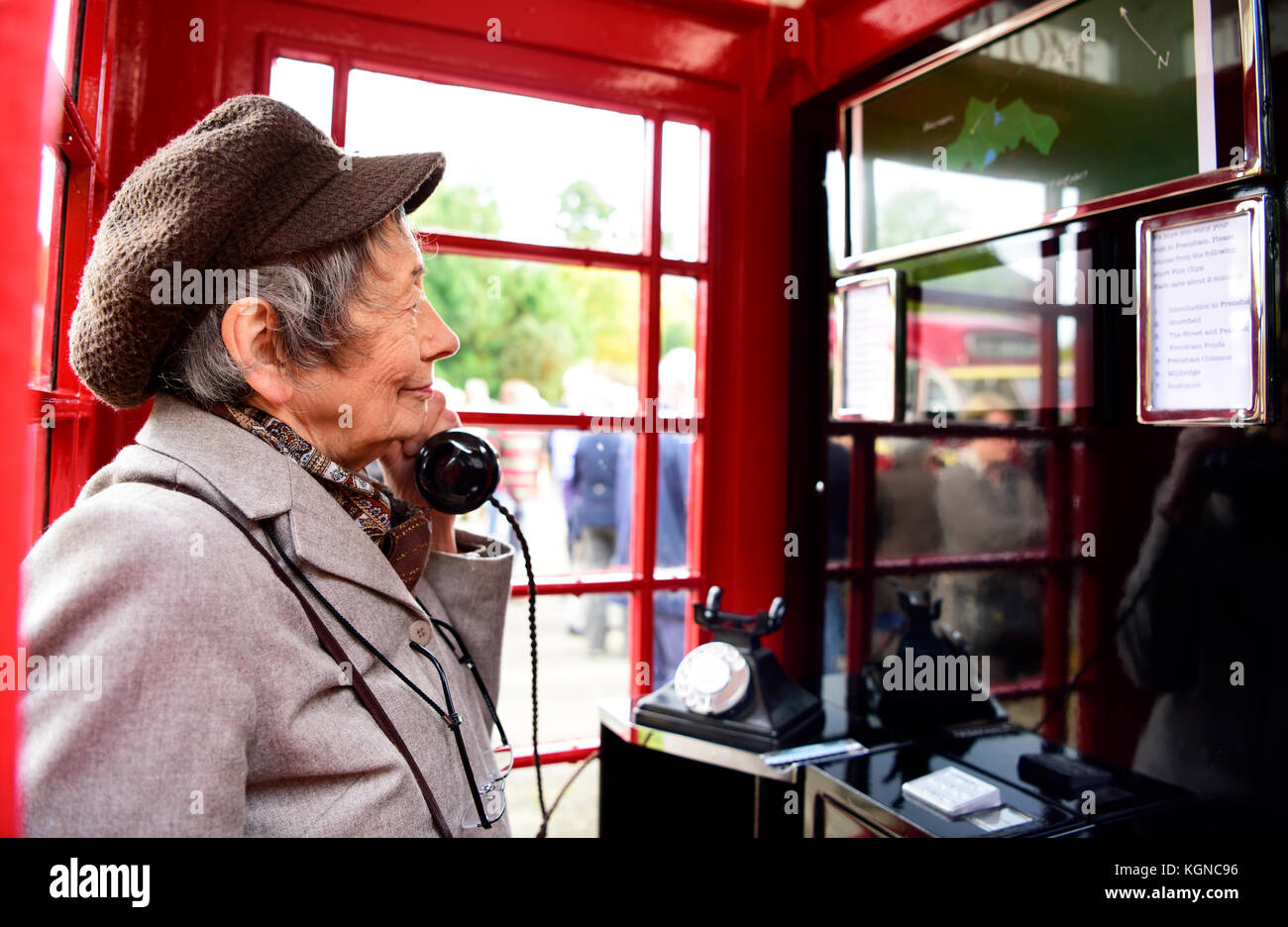 Elderly local resident using a traditional red phone box which has been converted into a small visitors centre. - Stock Image