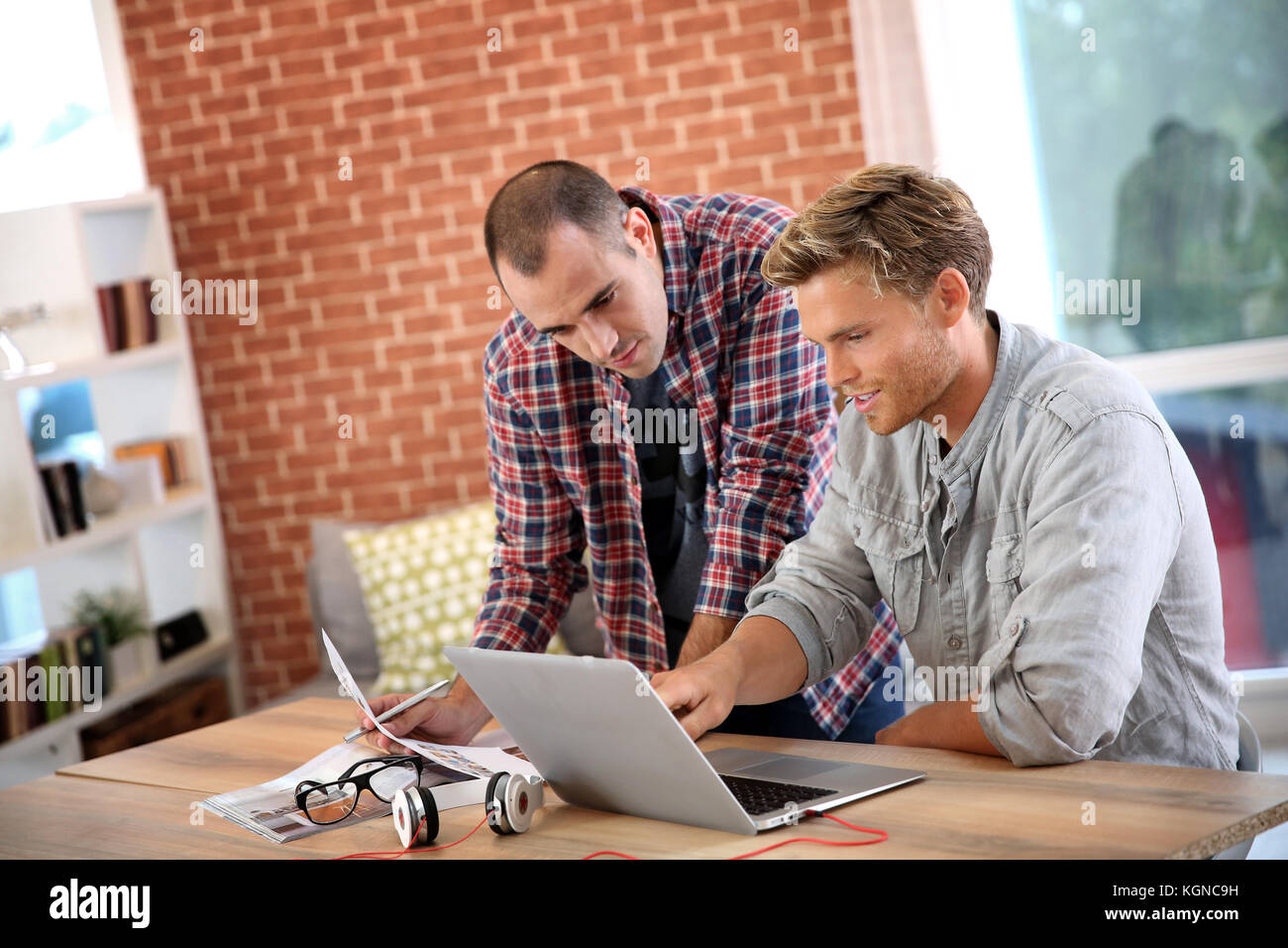 Young men studying in front of laptop - Stock Image