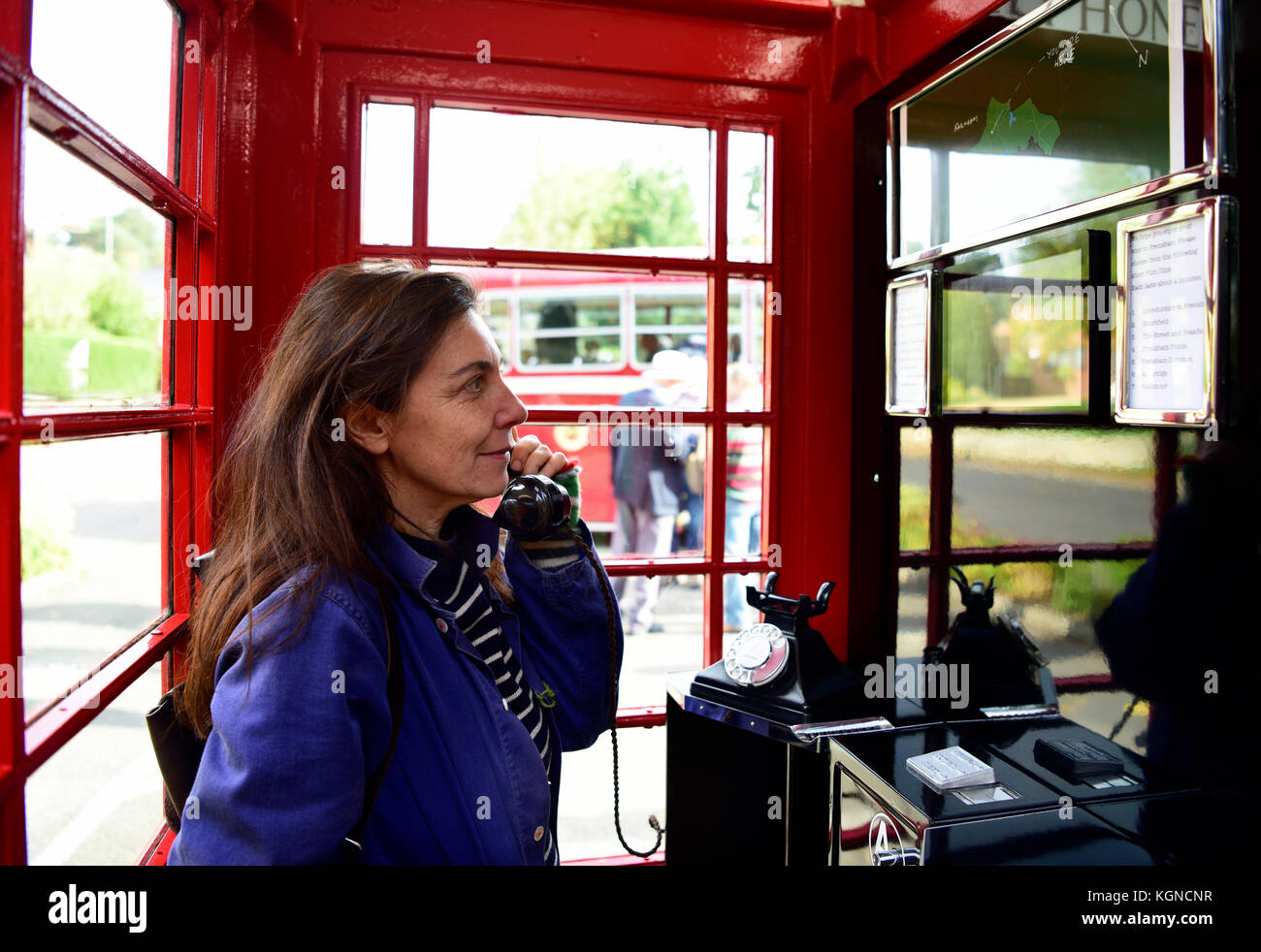 Female local resident using a traditional red phone box which has been converted into a small visitors centre. The - Stock Image