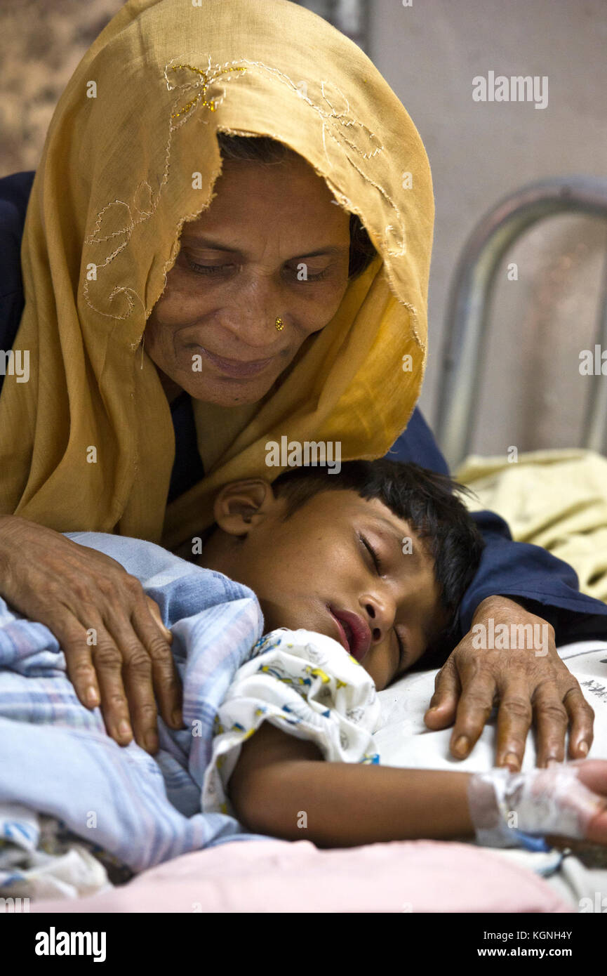 A Rohingya grandmother comforts her sleeping granddaughter while being treated at the new Rohingya Care Unit of - Stock Image