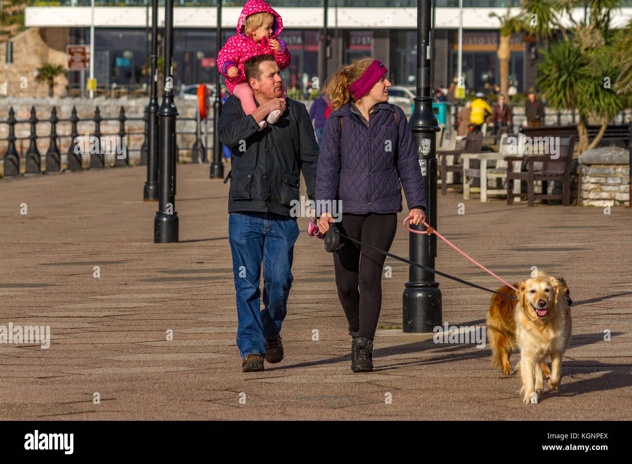 A family including a couple, with their young child on the man's shoulders, and their pet dog, walking along Torquay Stock Photo