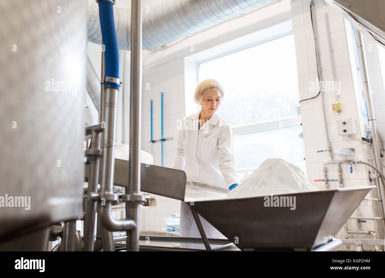 woman working at ice cream factory conveyor - Stock Image