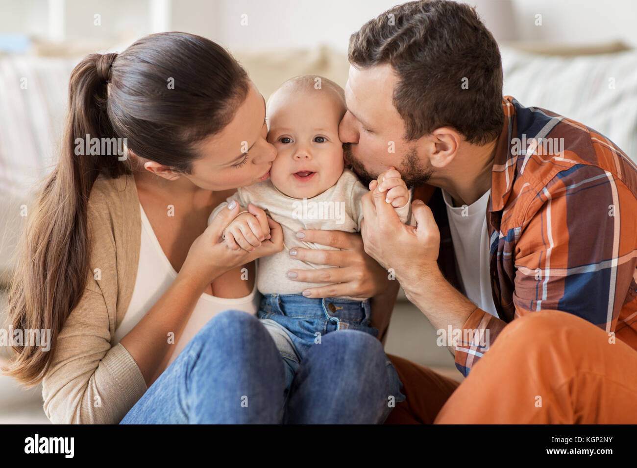 happy mother and father kissing baby at home - Stock Image