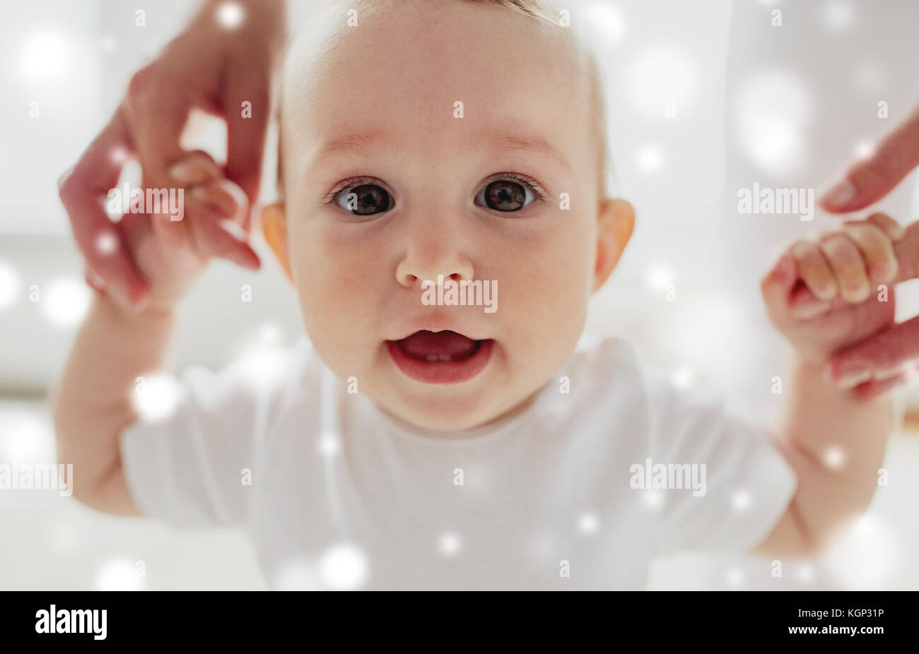 happy baby learning to walk with mother help - Stock Image