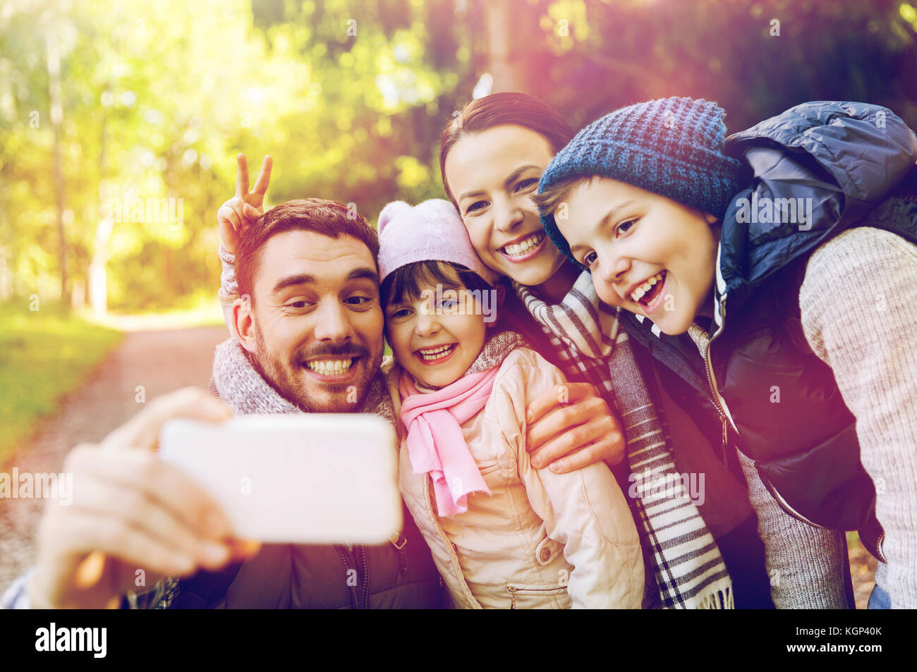 happy family taking selfie by smartphone outdoors - Stock Image