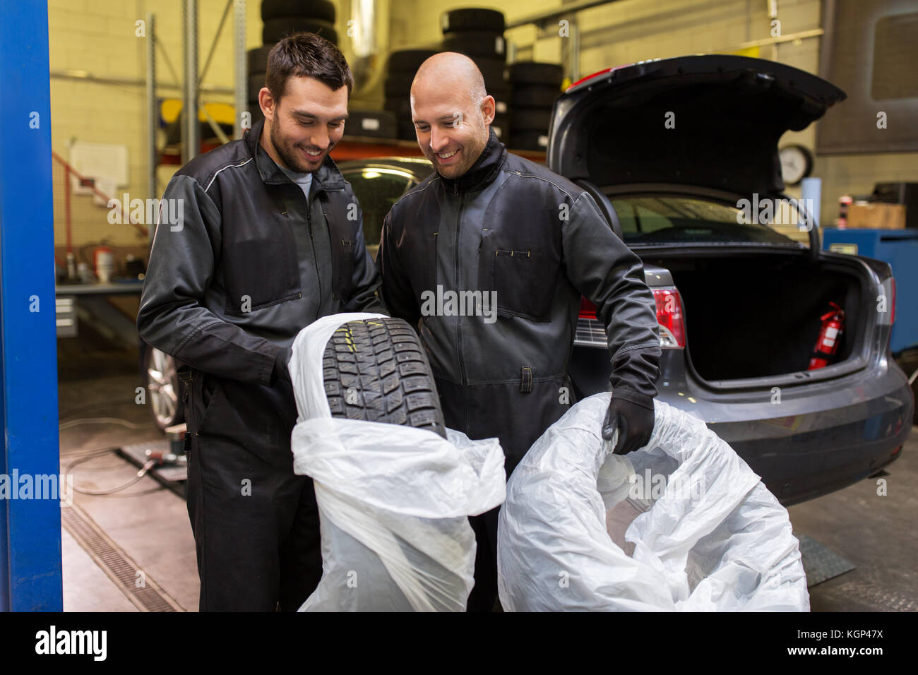 auto mechanics changing car tires at workshop - Stock Image