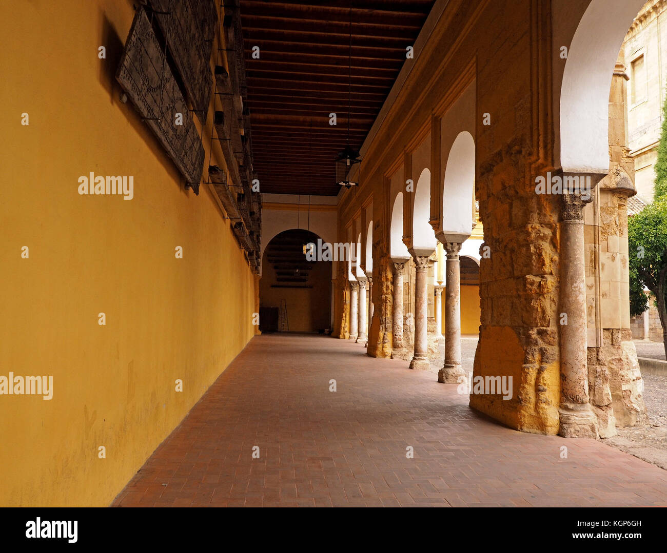 covered walkway with pillars alongside the Orange Tree Courtyard at the Great Mosque or Mosque Cathedral of Cordoba Stock Photo