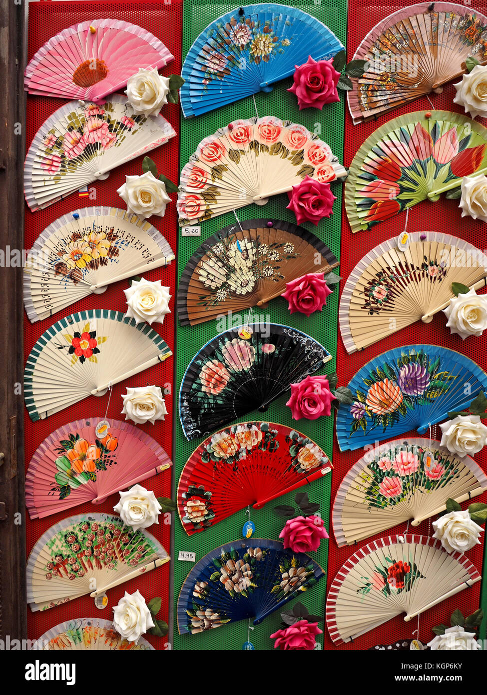 Display of colourful colorful Flamenco Spanish folding fans interspersed with red and white roses in Córdoba, - Stock Image