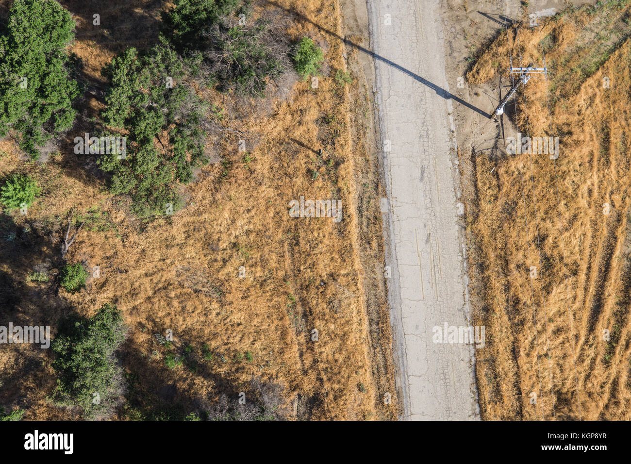 Drone view of empty lonely road in the wilderness of grassland and trees. - Stock Image