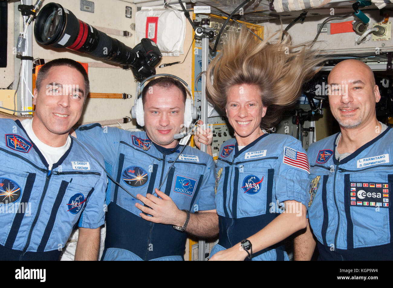 Expedition 36 flight engineers pose for a portrait in the Zvezda Service Module of the International Space Station. - Stock Image