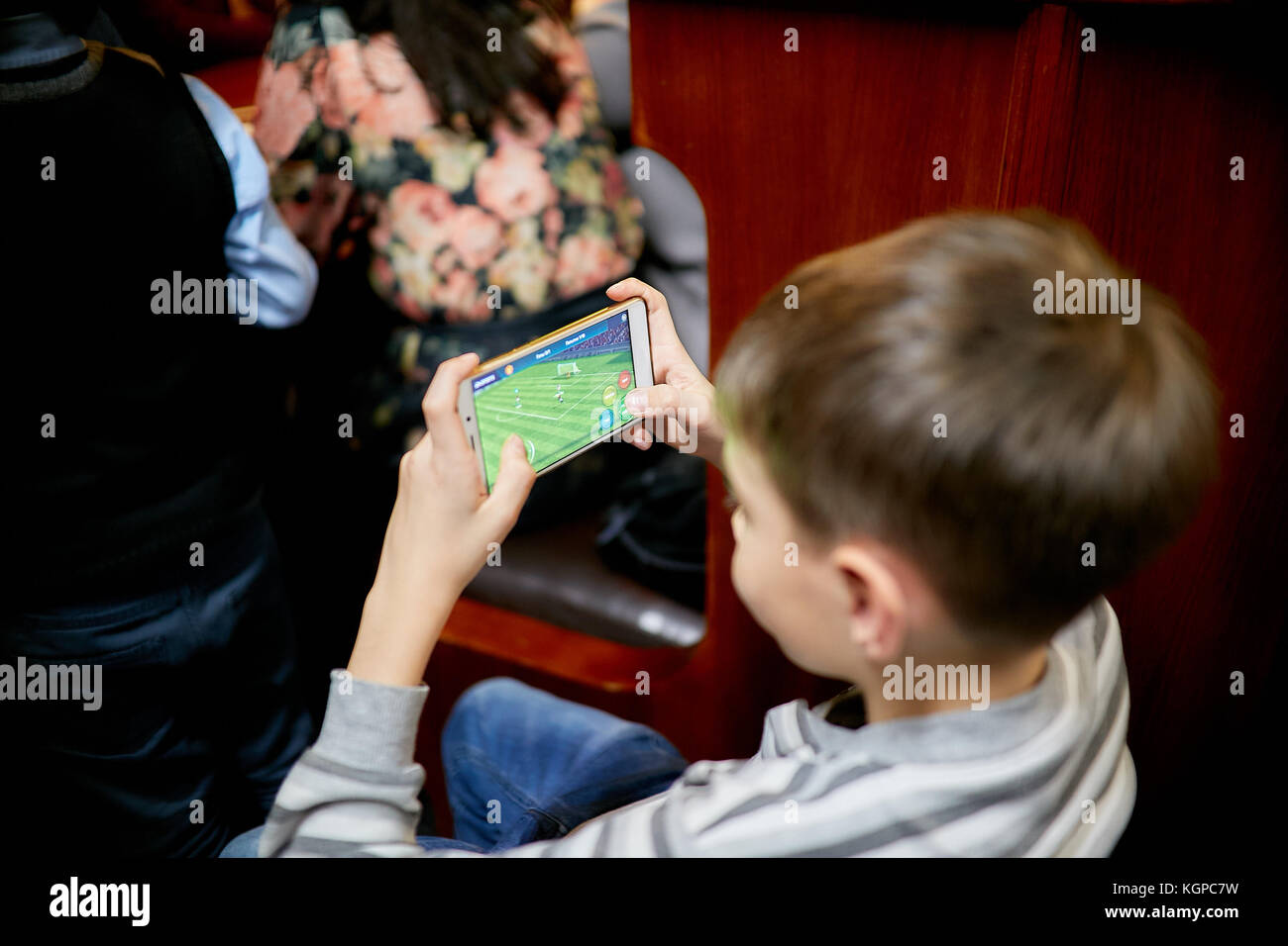 SYZRAN, RUSSIA, NOVEMBER 08, 2017: boy playing at mobile phone at home in football app - Stock Image