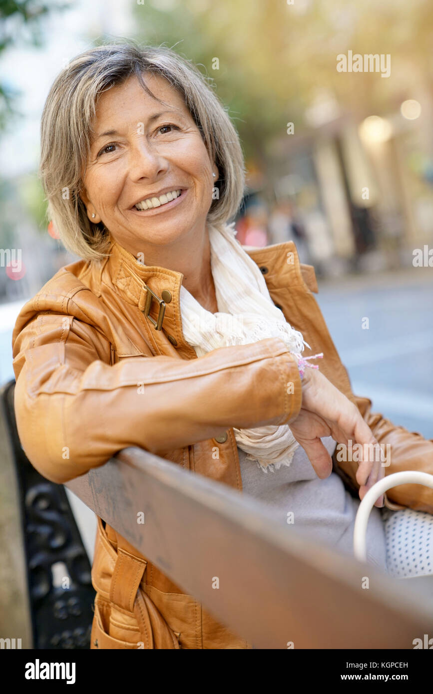 Senior woman on shopping day relaxing on bench - Stock Image