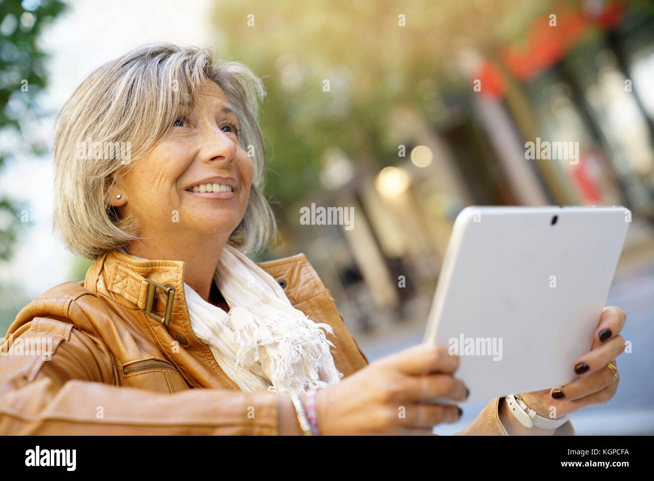 Senior woman in town using digital tablet - Stock Image