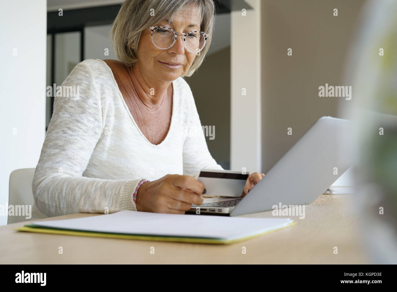 Senior woman buying on internet with credit card - Stock Image