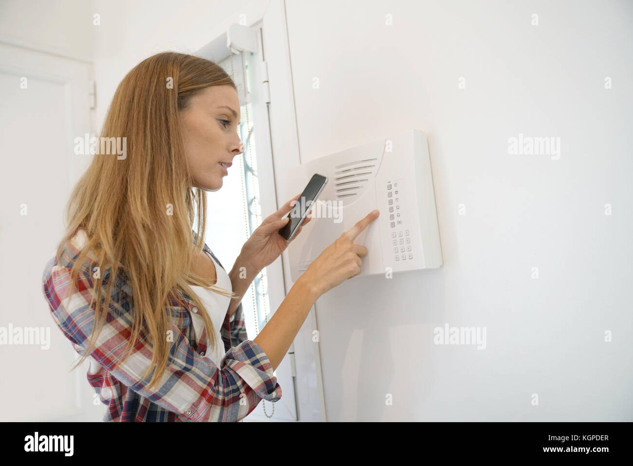 Woman programming home security alarm system Stock Photo